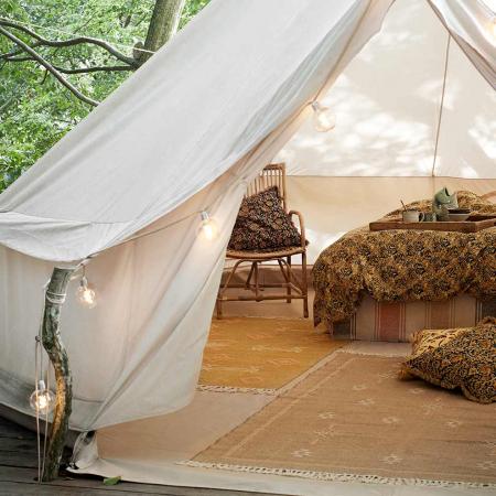 Glamping im Boho-Look - Teppiche und Bett in weißen großen Zelt