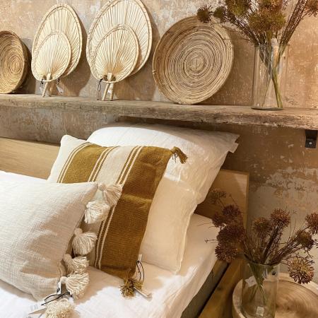 Scandi-Boho-Look - Bett mit Boho-Kissen  Palmblaettern und Trockenblumen